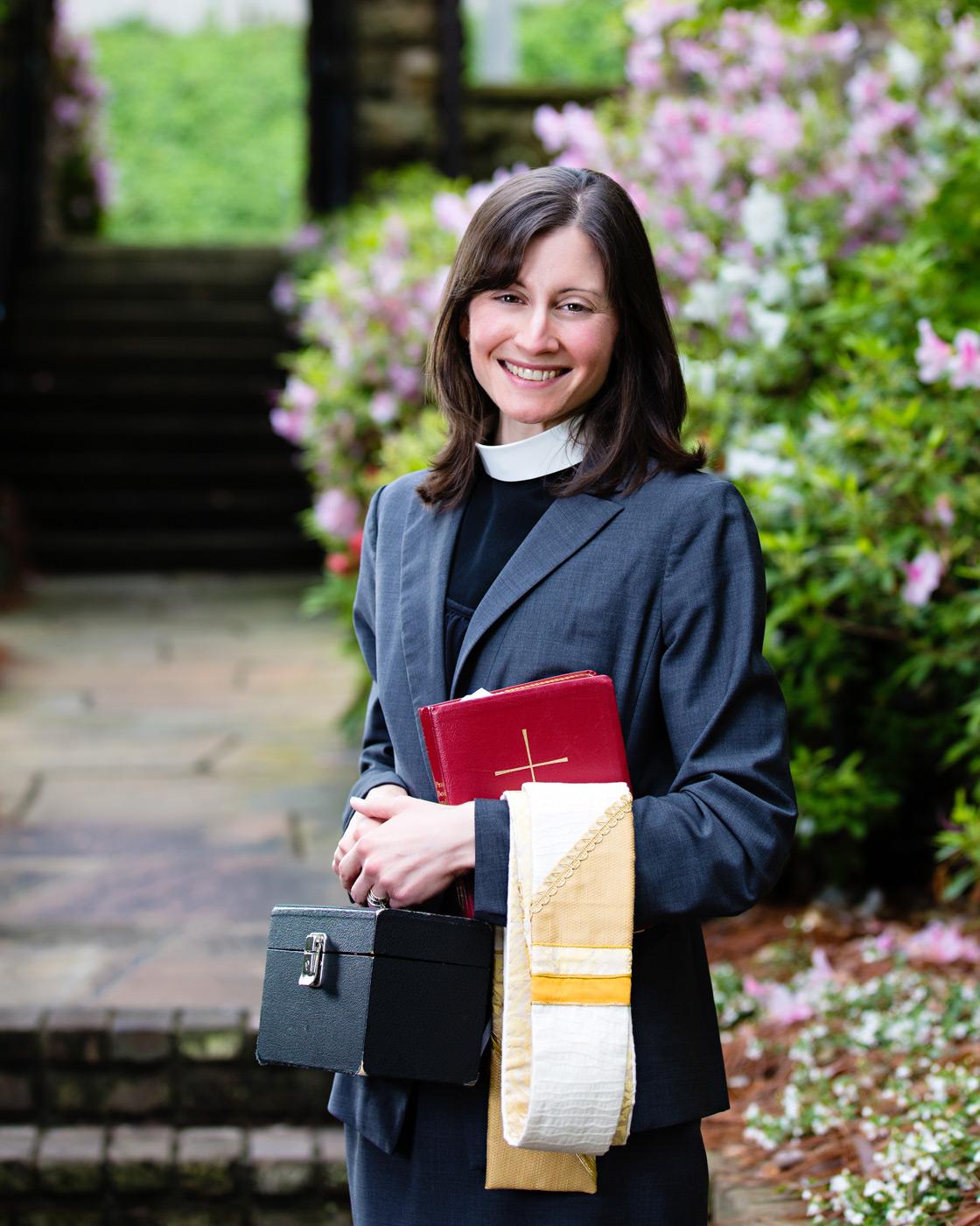 Female episcopal priest image in a church garden